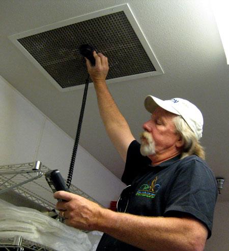 Don Ballard checks air flow in the intake room