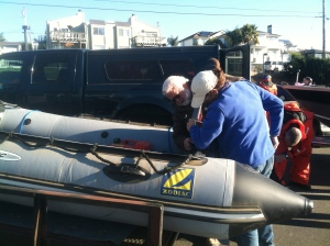 "Kyra Parker and Tim Williamson attaching the motor to the ""Purring Murre""."